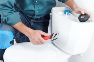 plumber working on a toilet